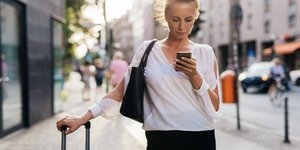 Nainen katsoo älypuhelinta ja nojaa matkalaukkuun