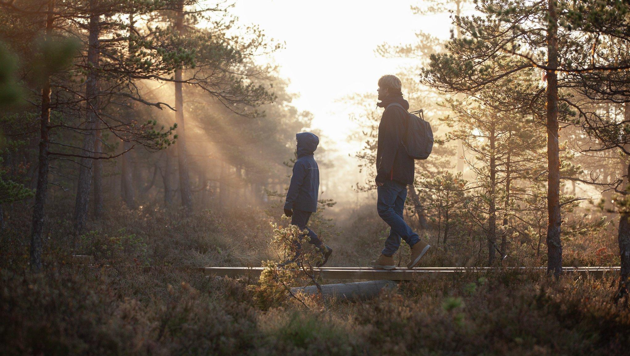 Mies ja lapsi kävelevät metsässä