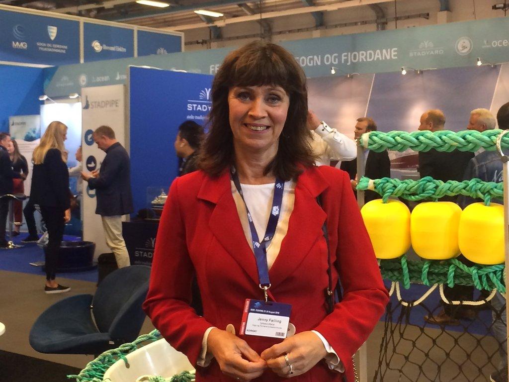 Jenny Følling står ved Sogn og Fjordane sin stand på fiskerimessa Nor-Fishing 2018. Garn, rep og anna maritimt utstyr heng bak henne.