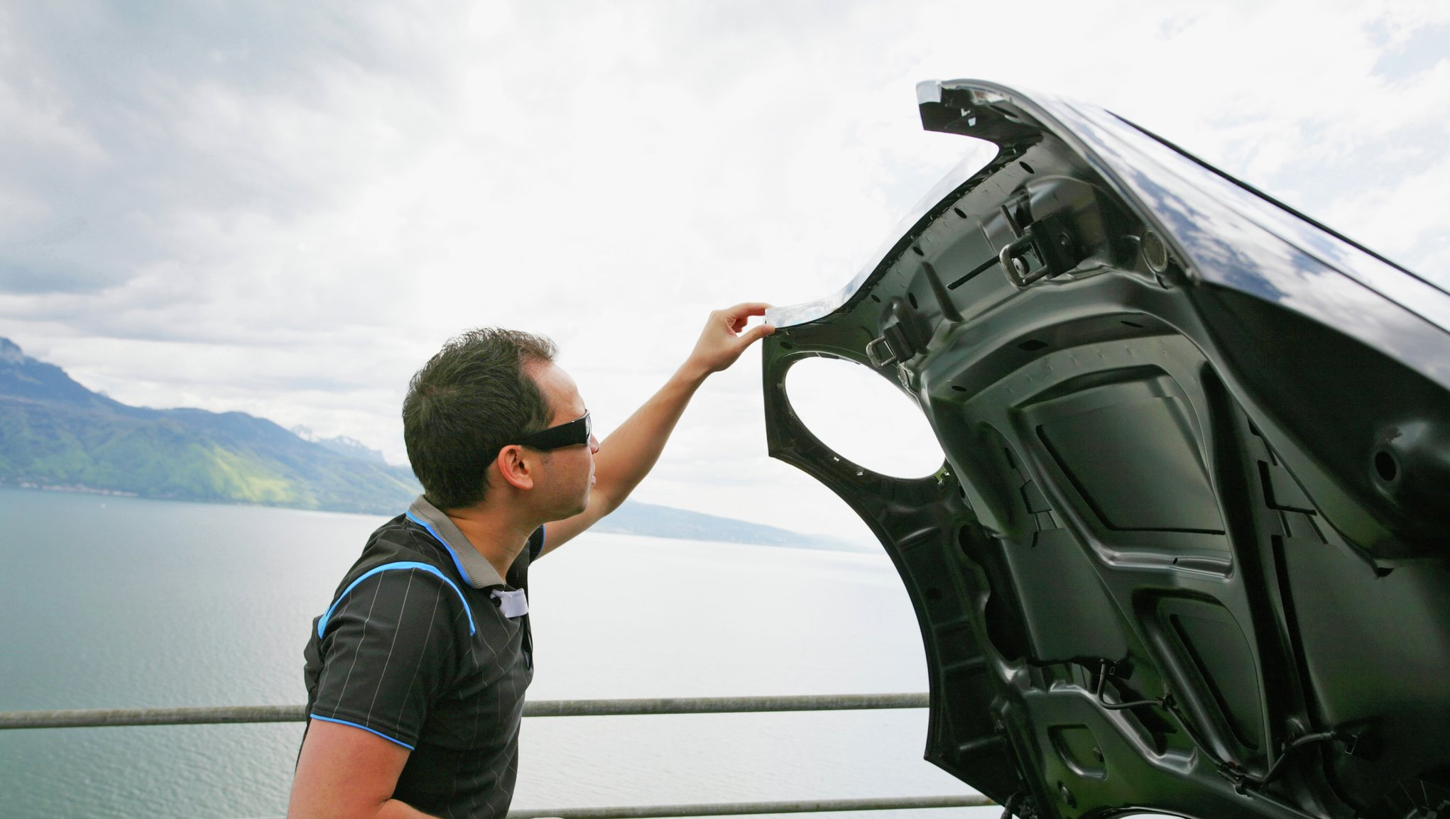 Mann som åpner panseret på en bil