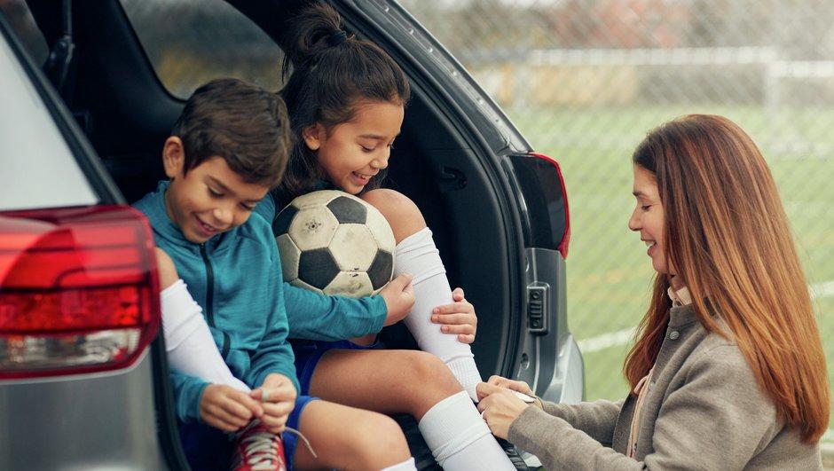 Äiti auttaa lapsia sitomaan kengännauhoja.