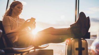 Nainen istuu penkillä lentokentällä jalat matkalaukun päällä