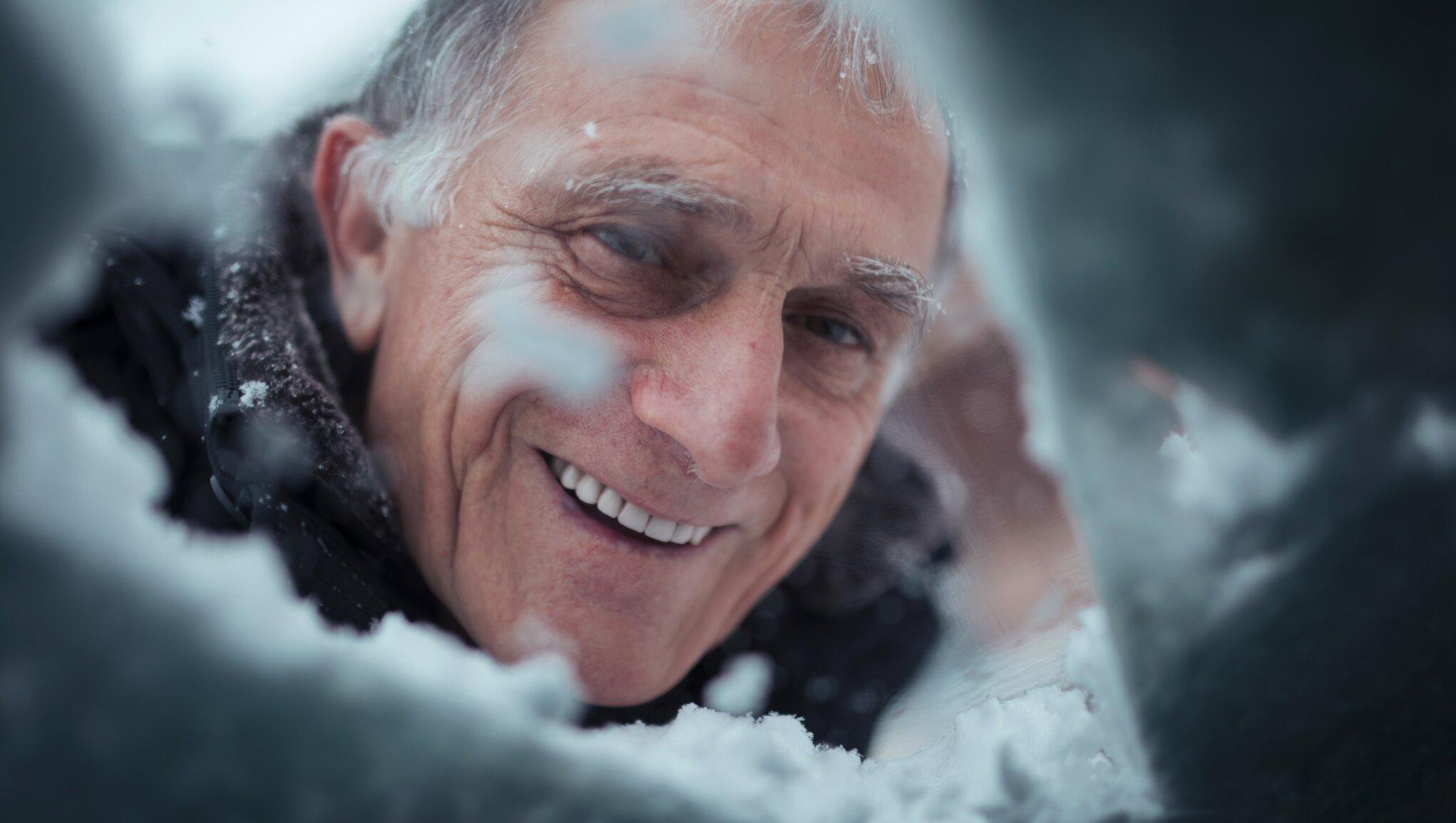 man tittar in genom snöig biltruta