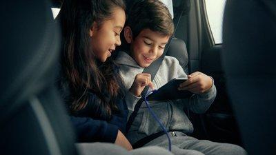 Barn i bil som ser på iPad