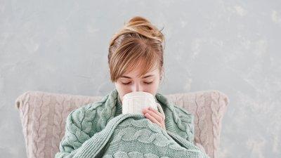 Nainen juo lämmintä juomaa peittoon kääriytyneenä
