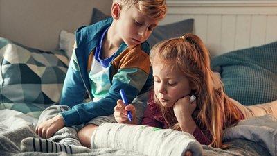 flicka skriver på brors gips