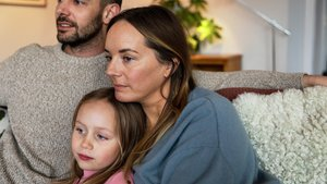 Perhe katselee televisiota sohvalla