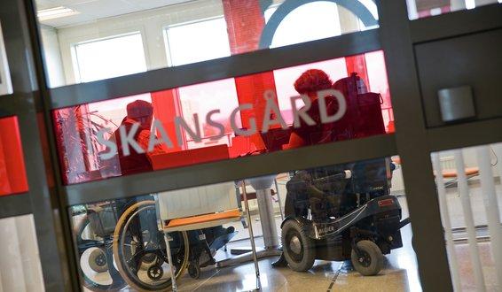 To medarbeidere i rullestol sett gjennom glassdør