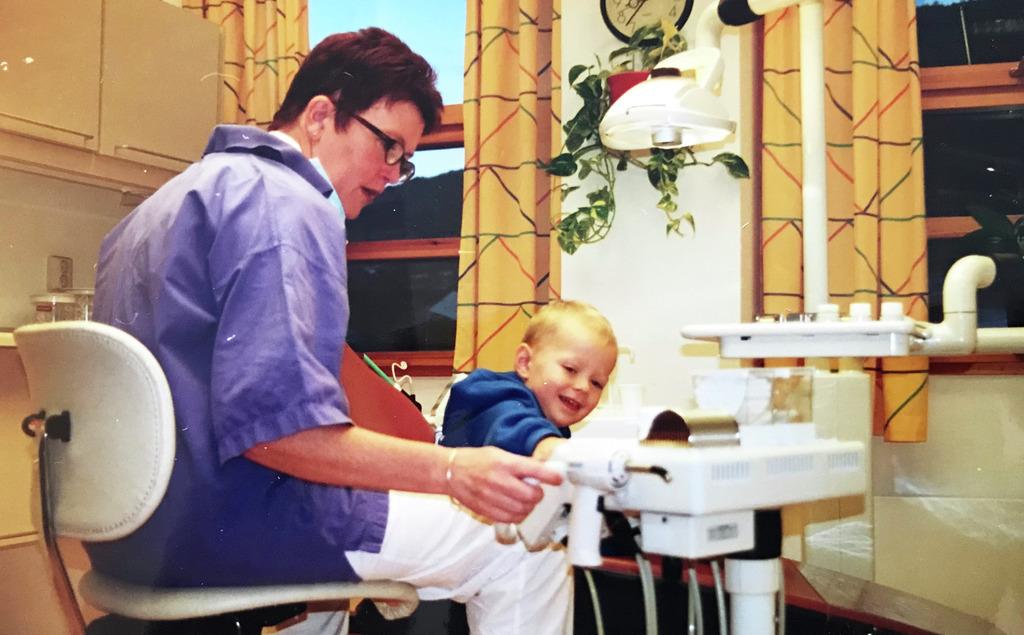 Foto av tannpleiar Britt Sønnesyn med ein blid, lyshåra, treårig pasient i tannpleiarstolen.