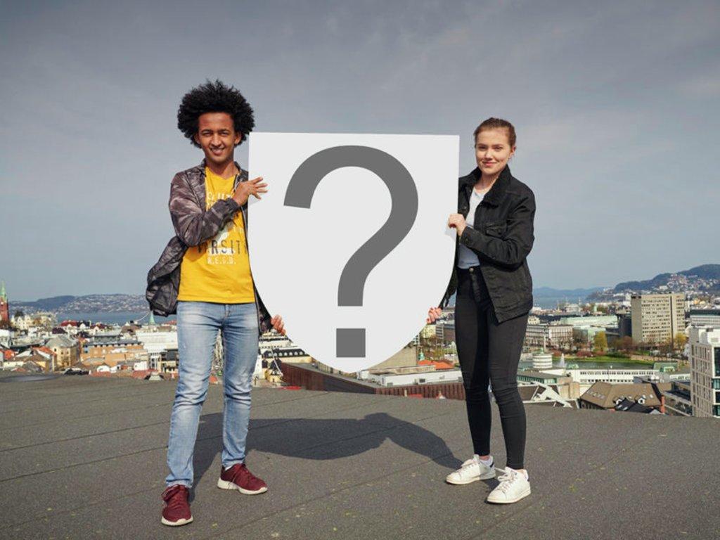 To ungdomar står på taket på fylkeshuset i Bergen med utsikt mot byen og fjorden. Dei held eit stort våpenskjold med eit grått spørjeteikn på kvit bakgrunn.