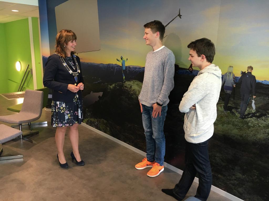 Foto av fylkesordførar Jenny Følling som står og snakkar med to unge gutar framfor ein vegg som er kledd med fototapet. Fotoet syner unge menneske oppå ein fjelltopp.