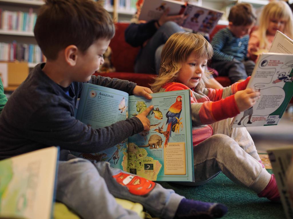 Foto av to små ungar på eit bibliotek, ein gut med mørkt hår og ei jente med lysare hår. Dei ser begeistra i kvar si bok, og guten peikar på ein av teikningane i boka.