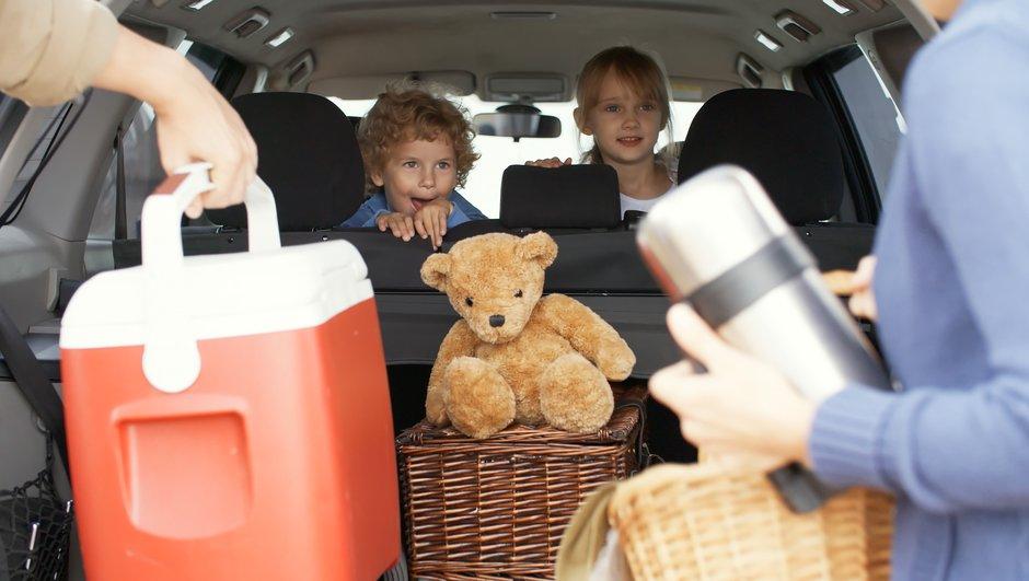 Lapset odottavat autossa, jonne vanhemmat pakkaavat eväitä.