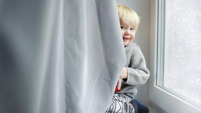 Ett barn tittar fram bakom en gardin