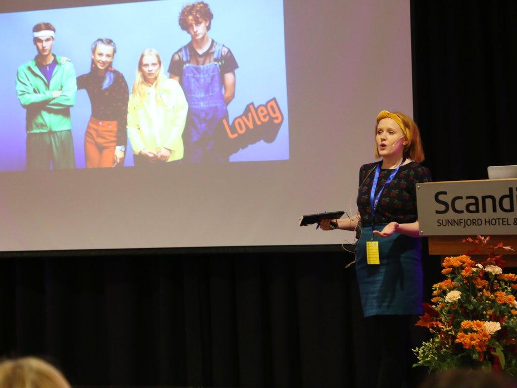 Forfattar Kjersti Wøien Håland på scenen under språkkonferansen i Førde. Bak henne er det vist eit bilete frå tv-serien Lovleg.