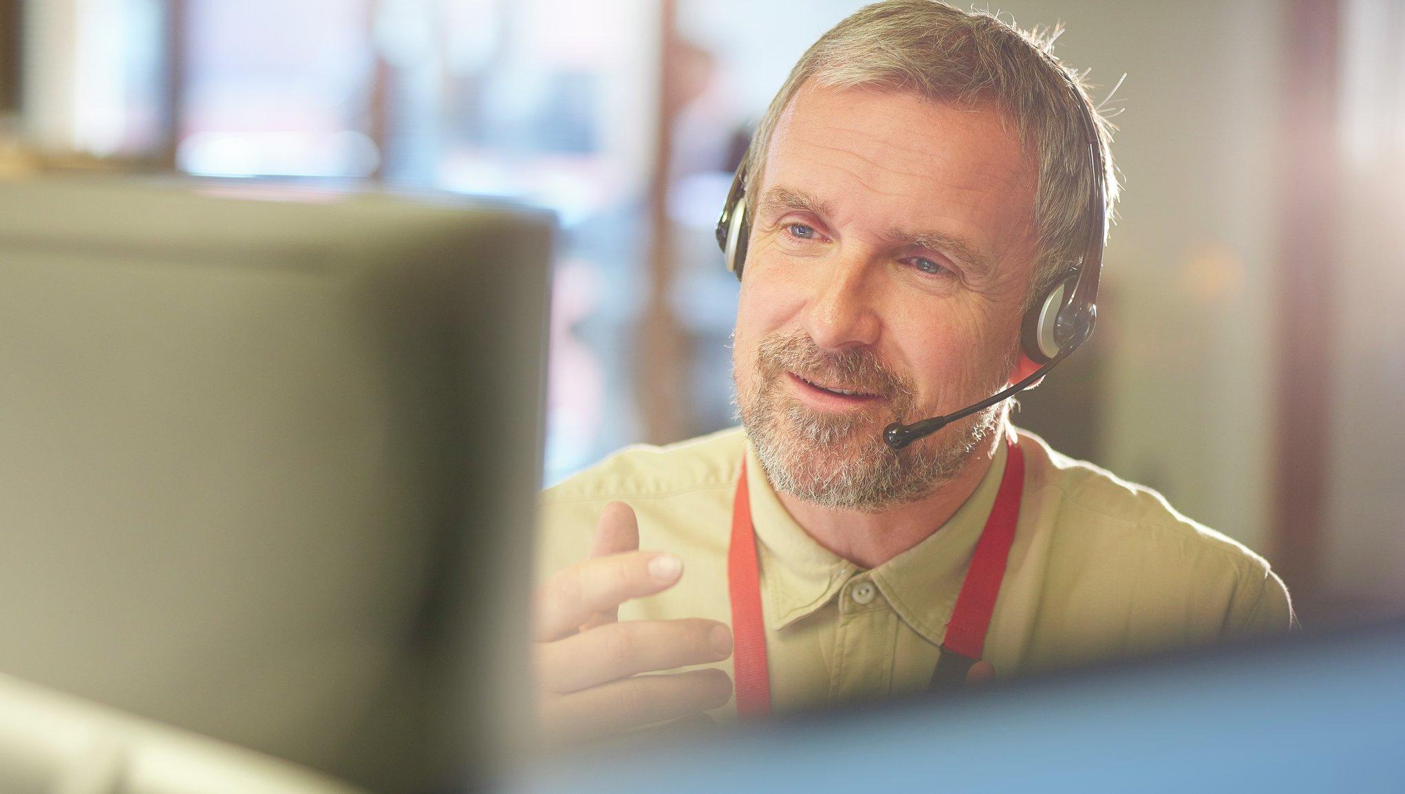 Mies istuu tietokoneella kuulokkeet päässä