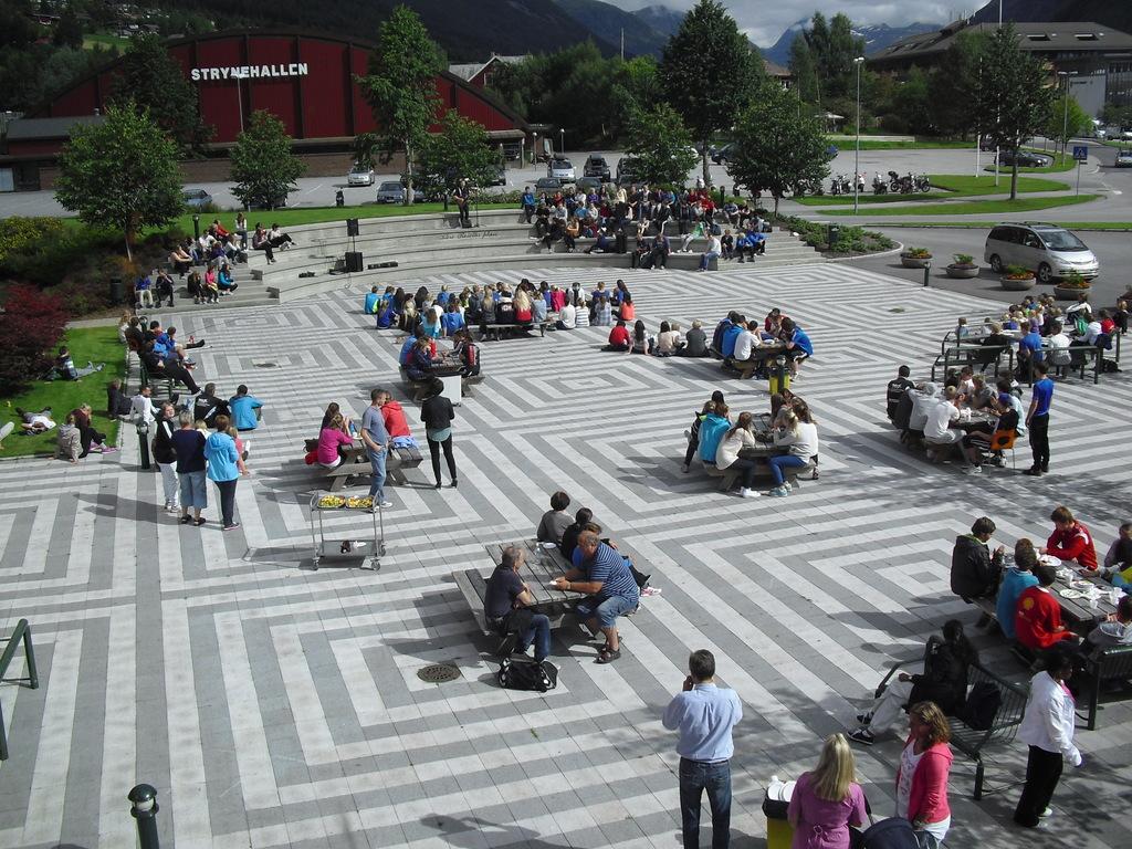 Foto som syner plassen utanfor Stryn vidaregåande skule. Det sit elevar ved mange av borda på plassen.