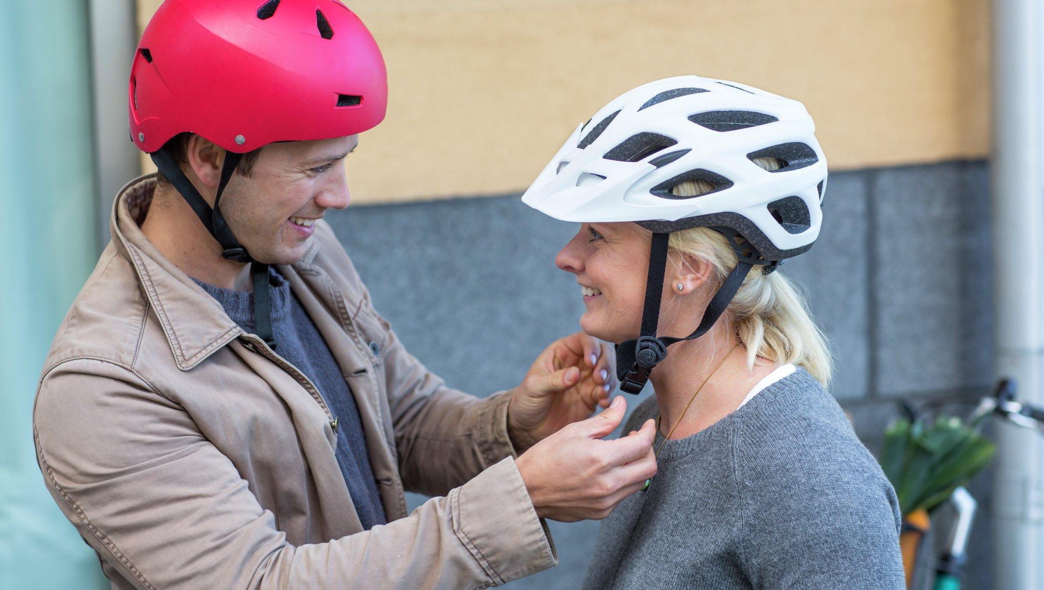 Mies auttaa naista laittamaan pyöräilykypärää päähän