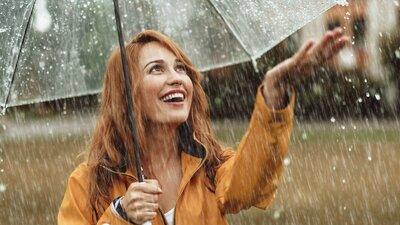 Nainen seisoo sateella sateenvarjon alla