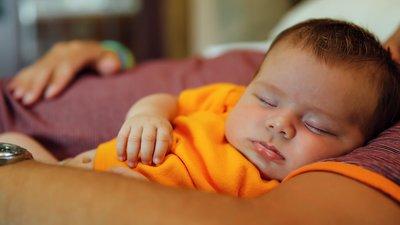 vauva nukkuu sylissä