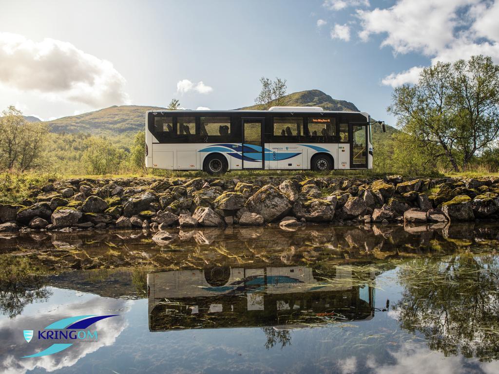 Foto av ein buss med kringom-dekor som køyrer i irrgrønt landskap. Bussen køyrer forbi og blir spegla i eit vatn. Kringom-logoen er nedst til venstre på biletet.