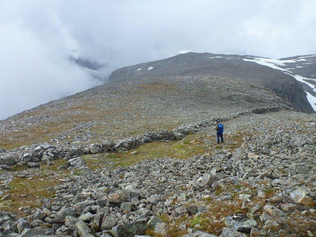 Bilete av ein steinmur som går langs fjellsida og avsluttar ved eit stup.