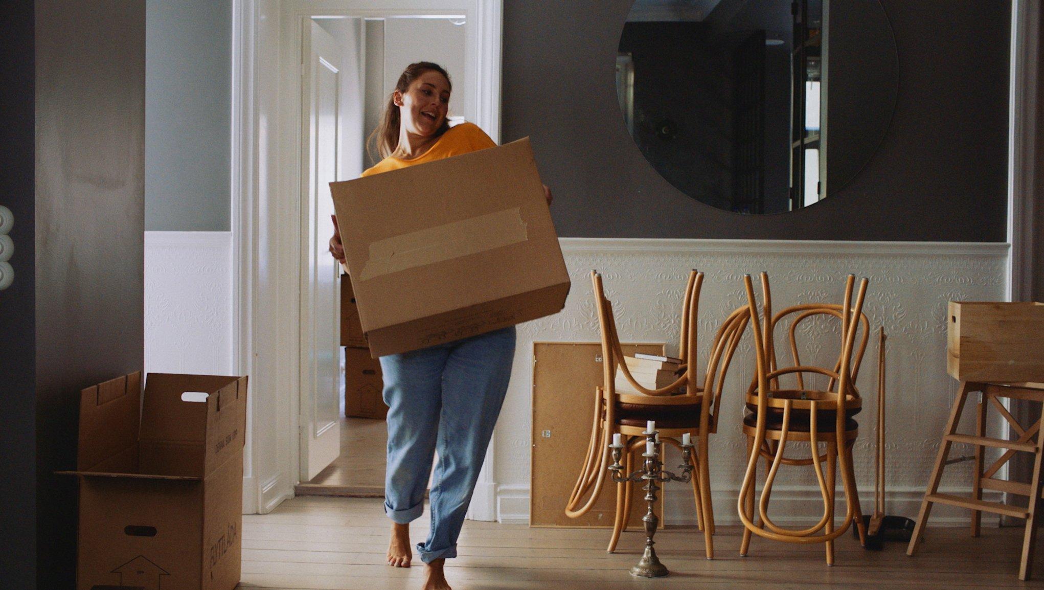 Kvinde der flytter en flyttekasse