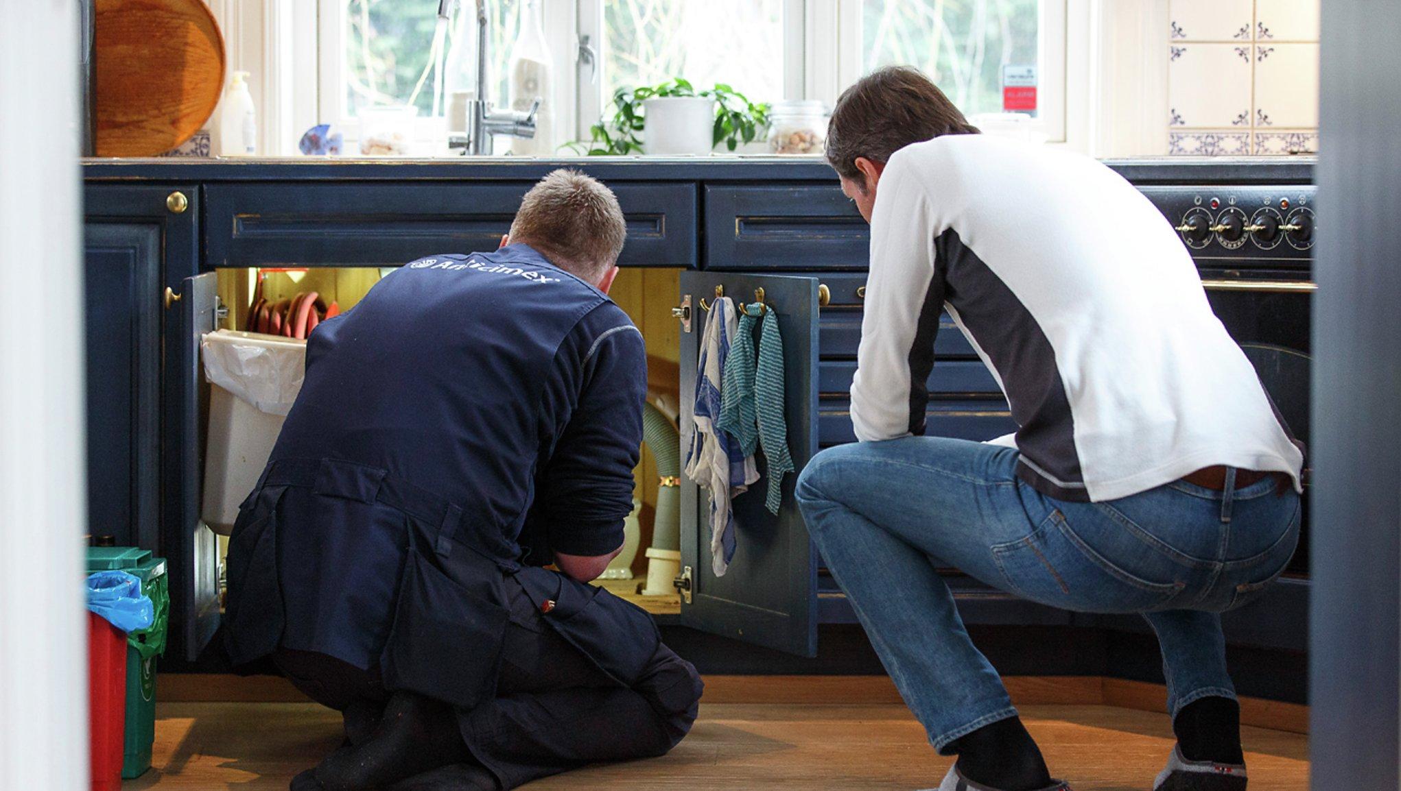 Kaksi miestä tarkastelevat keittiön allaskaappia