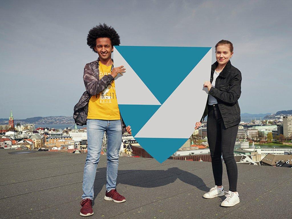 To ungdomar står på taket av fylkeshuset i Bergen og held ein modell av fylkesvåpenet for Vestland med utsikt over byen i bakgrunnen.