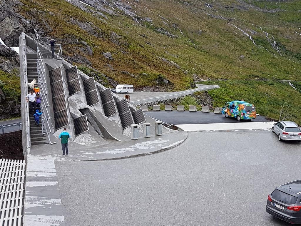 Foto frå utsikten på Gaularfjellet, nasjonal turistveg. Biletet er teke ovanfrå, og vi ser vire bilar som er i ferd med å køyre nedover. Det er nokre personar i trappene i monumentet.