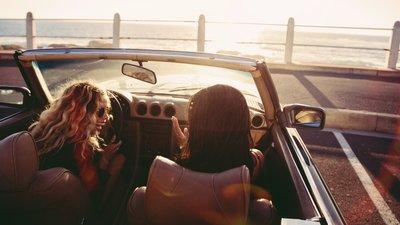 Kaksi naista avoauton kyydissä meren rannalla