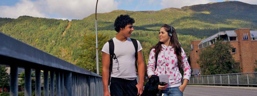 Foto av to ungdomar, ei jente og ein gut, gåande over ei bru i Førde. Dei snakkar saman, ho har øyretelefonar på og han ber ei brusflaske.