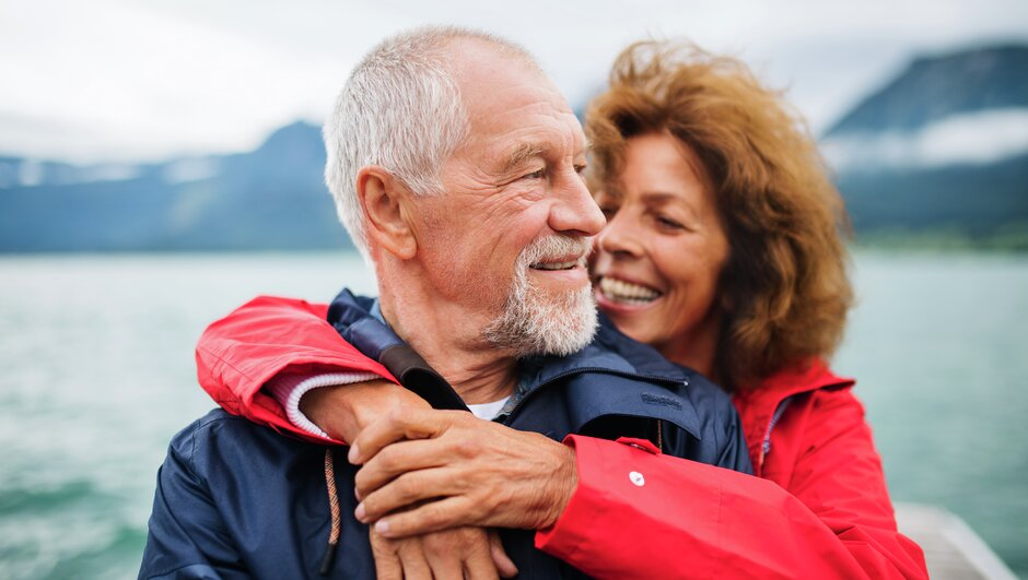 Man and woman hugging in front of an ocean.