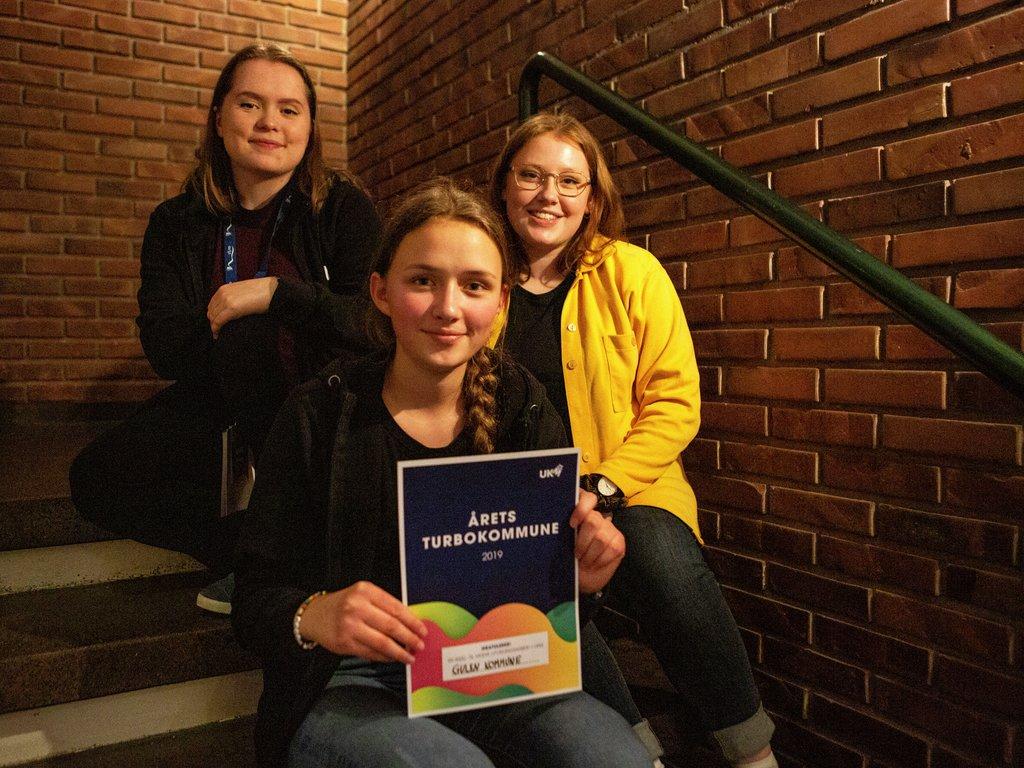 Foto av tre unge jenter som sit i ei trapp, med teglsteinsveggar bak. Ho som sit fremst held eit diplom der det står Årets turbokommune 2019.