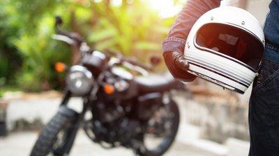 Moottoripyöräkypä kuskin kainalossa ja moottoripyörä taustalla