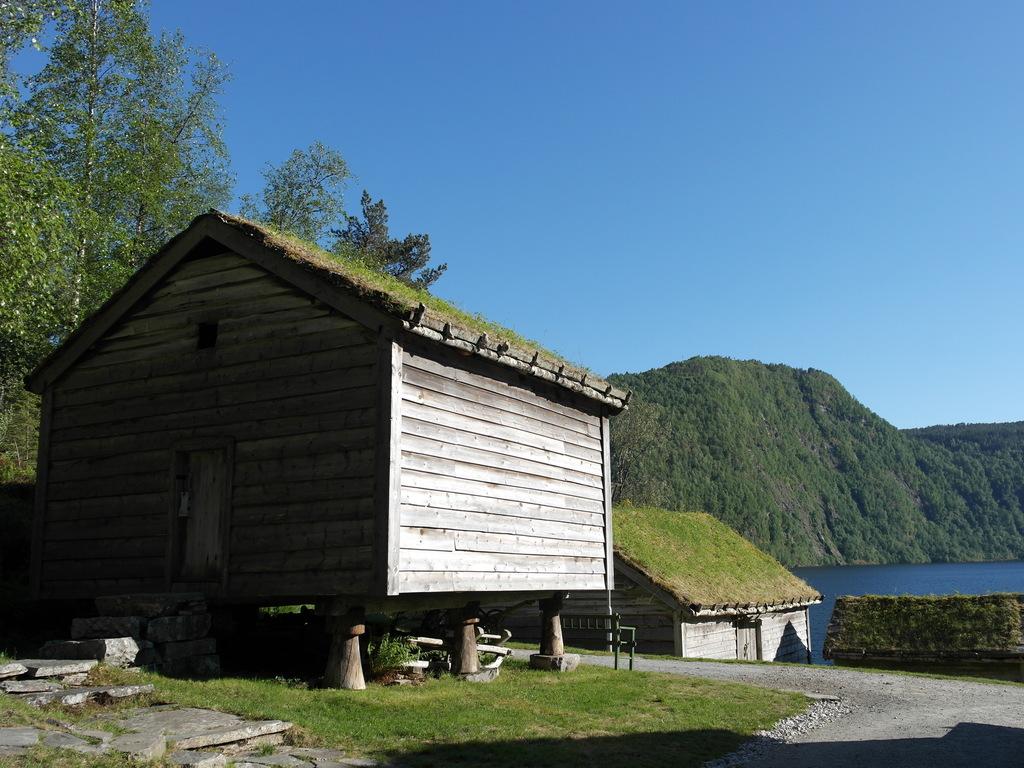 Foto frå Sunnfjord Museum ein strålande sommardag med blå himmel. Vi ser gamle hus med torvtak, blå himmel og har utsikt mot vatnet.