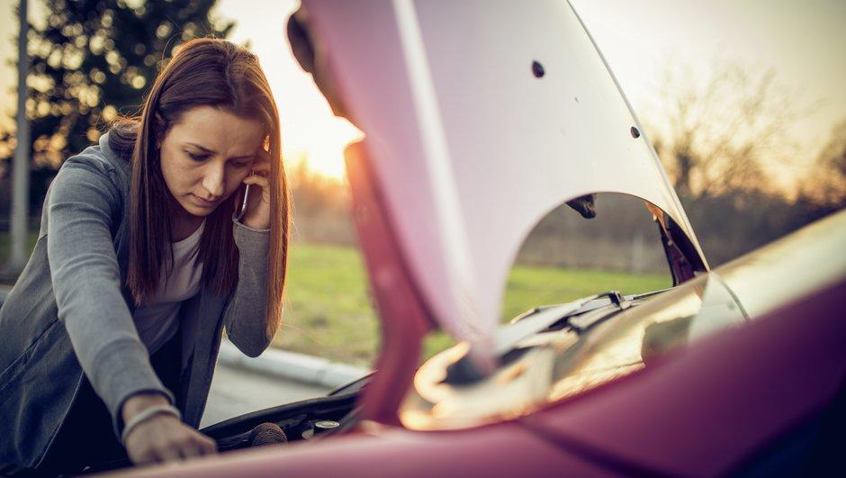 Nainen katsoo konepellin alle