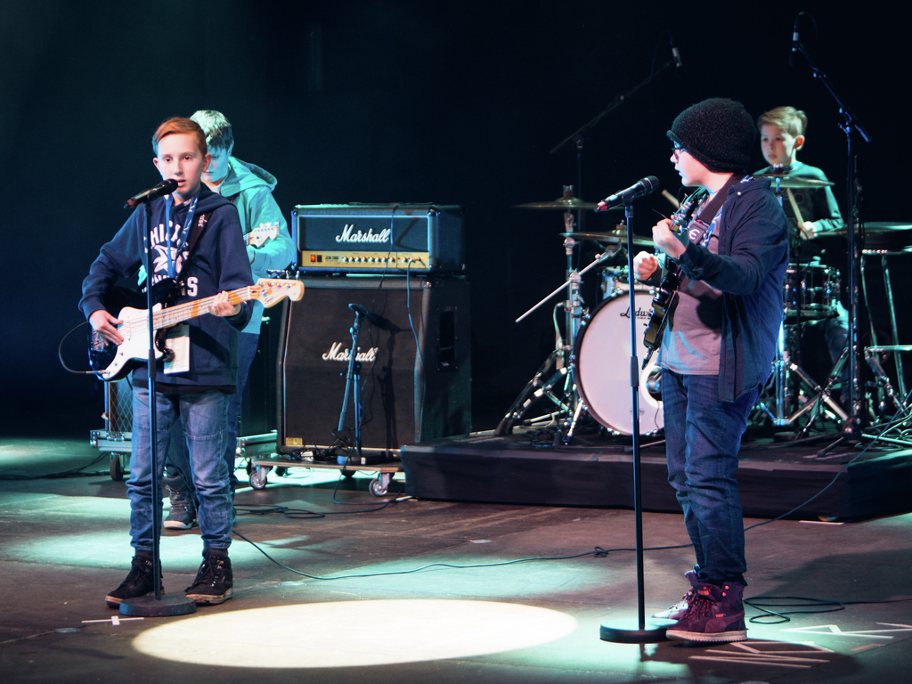 Foto av gruppa Fjernlys på UKM i 2017. Det er fire unge gutar, som spelar gitar, bass, trommer og syng.