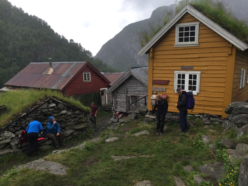 Foto frå garden Sinjarheim i Aurlandsdalen. Vi ser fleire av bygningane på garden og fleire personar som går rundt på og et nista si på området.