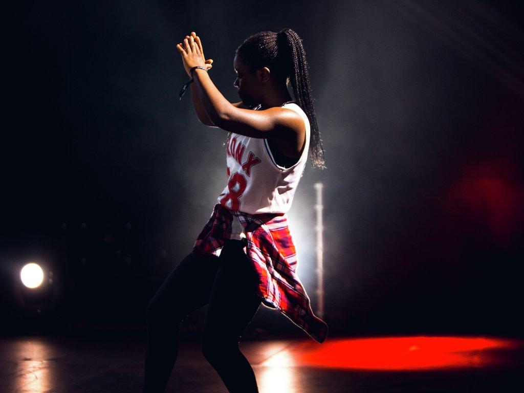 Foto av jente som dansar under UKM-festivalen 2017. Det er mørkt rundt ho, men noko raudt lys i bakgrunnen.