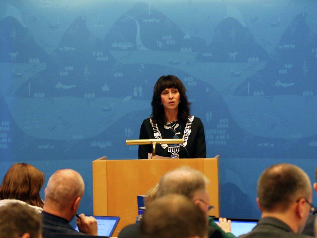 Fylkesordførar Jenny Følling på talarstolen i Firdasalen på Fylkeshuset. Ho har på seg fylkesordførarkjedet med fylkesvåpenet.