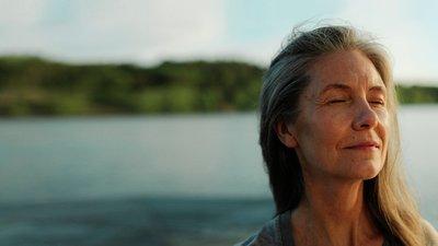 En äldre kvinna yogar vid vatten