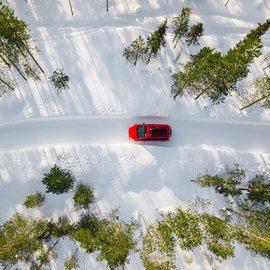 Auto kulkee lumisella tiellä