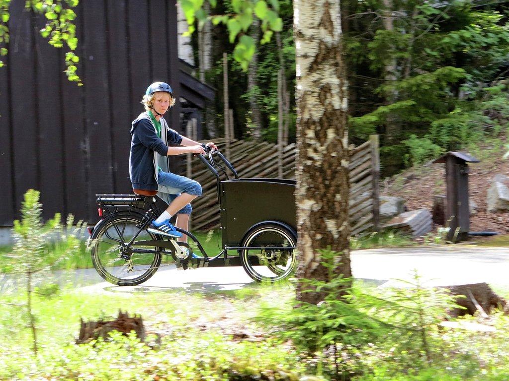 Foto av ein ungdom som syklar på ein elsykkel med lastekasse framme.