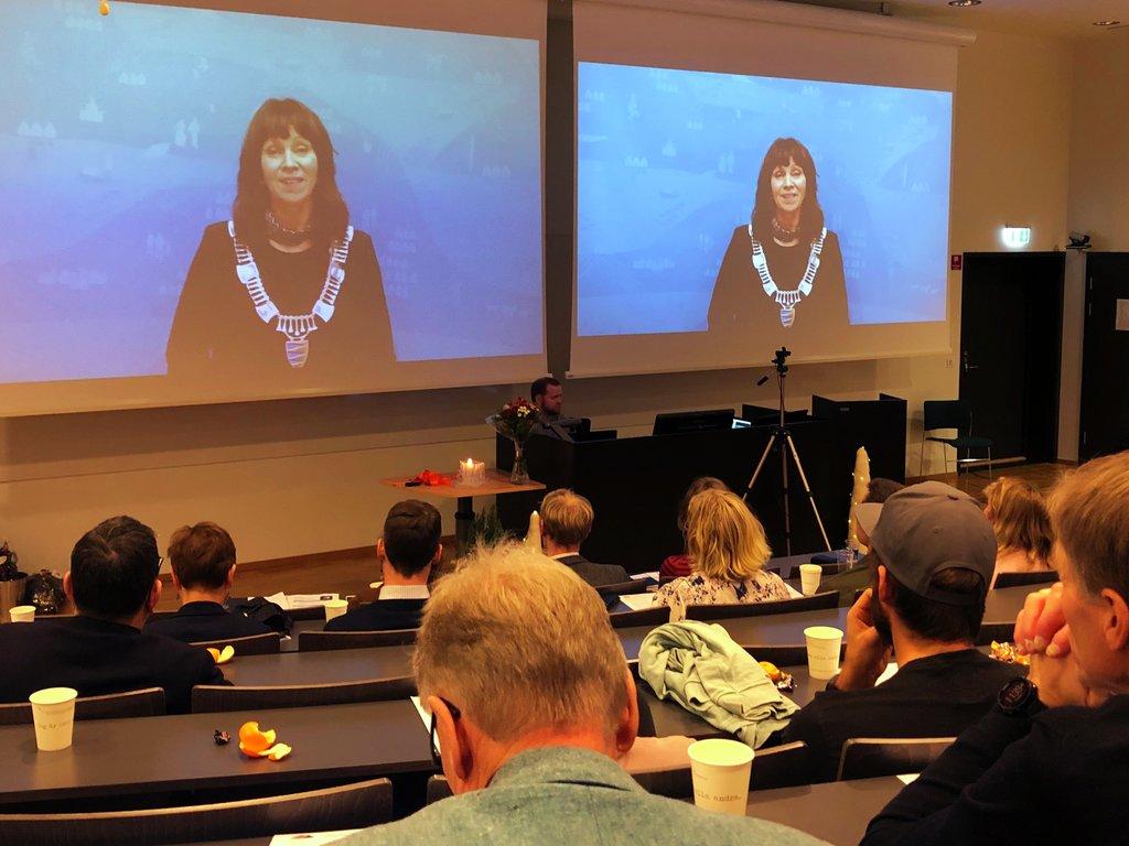 Folk sit i eit auditorium og ser mot ein skjerm der fylkesordførar Jenny Følling talar via video.
