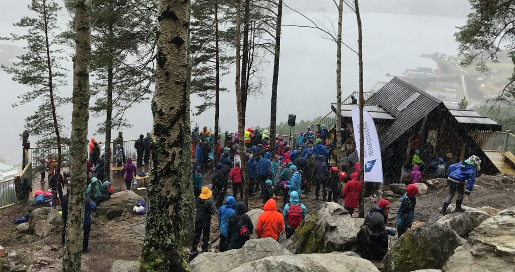 Foto teke over dagsturhytta i Gloppen på opningsdagen 8. desember 2017. Hytta ligg i Trivselsskogen på Sandane. Vi ser ned mot hytta, der det er samla mykje folk, og vidare ned mot fjorden.