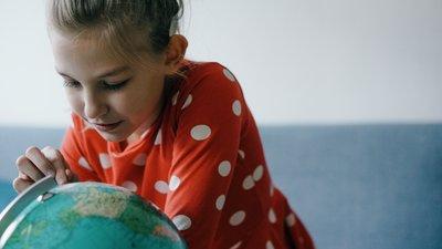 Jente som ser på en globus