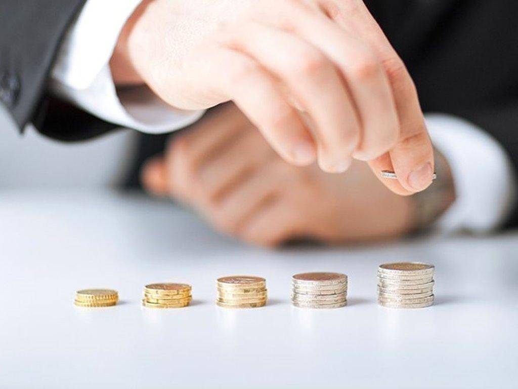 Foto av hender som sorterer stablar med pengar.