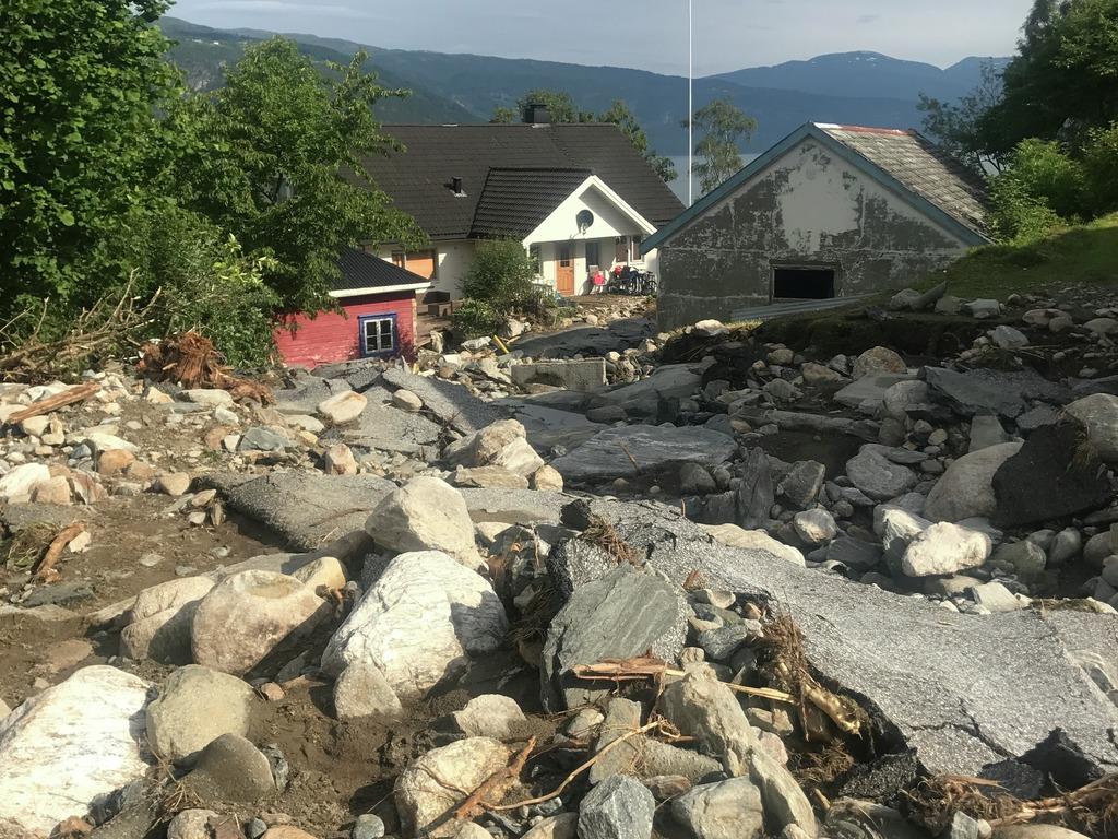 Foto av øydelagt veg i Utvik etter flaum og ekstremver 25. juli 2017. Asfalt er nesten heilt vekke, grus og stein, to hus i bakgrunnen. Sol.