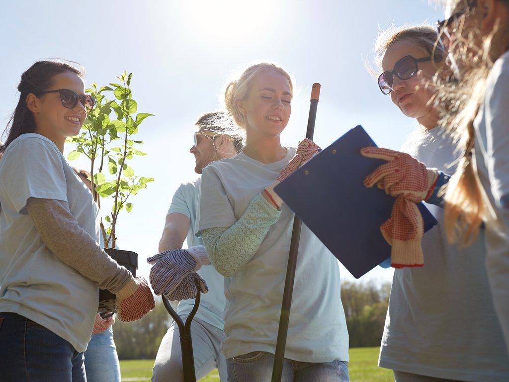 Foto av ungdomar som står og held planter og spadar osv., medan dei ser ut til å få instruksjonar frå ei kvinne.